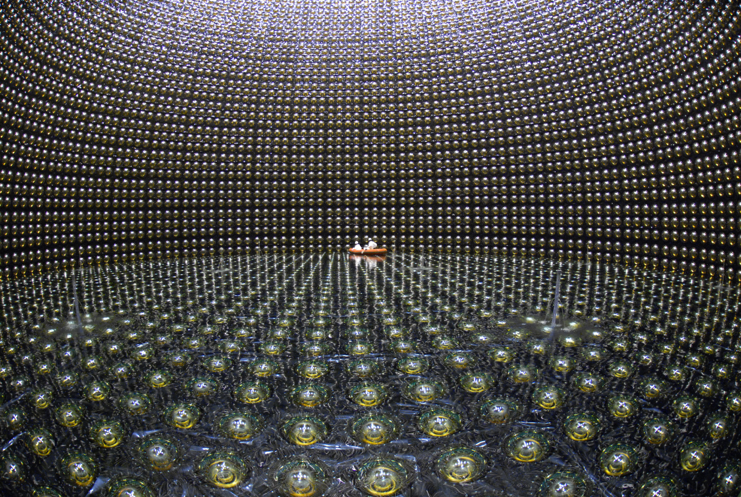 At the Super-Kamiokande observatory in Kamioka, Japan — shown here when it was being filled with water in 2006 — neutrinos interact with atoms inside the water, generating flashes of radiation that are picked up by the surrounding sensors and analyzed to determine the neutrinos' flavors.