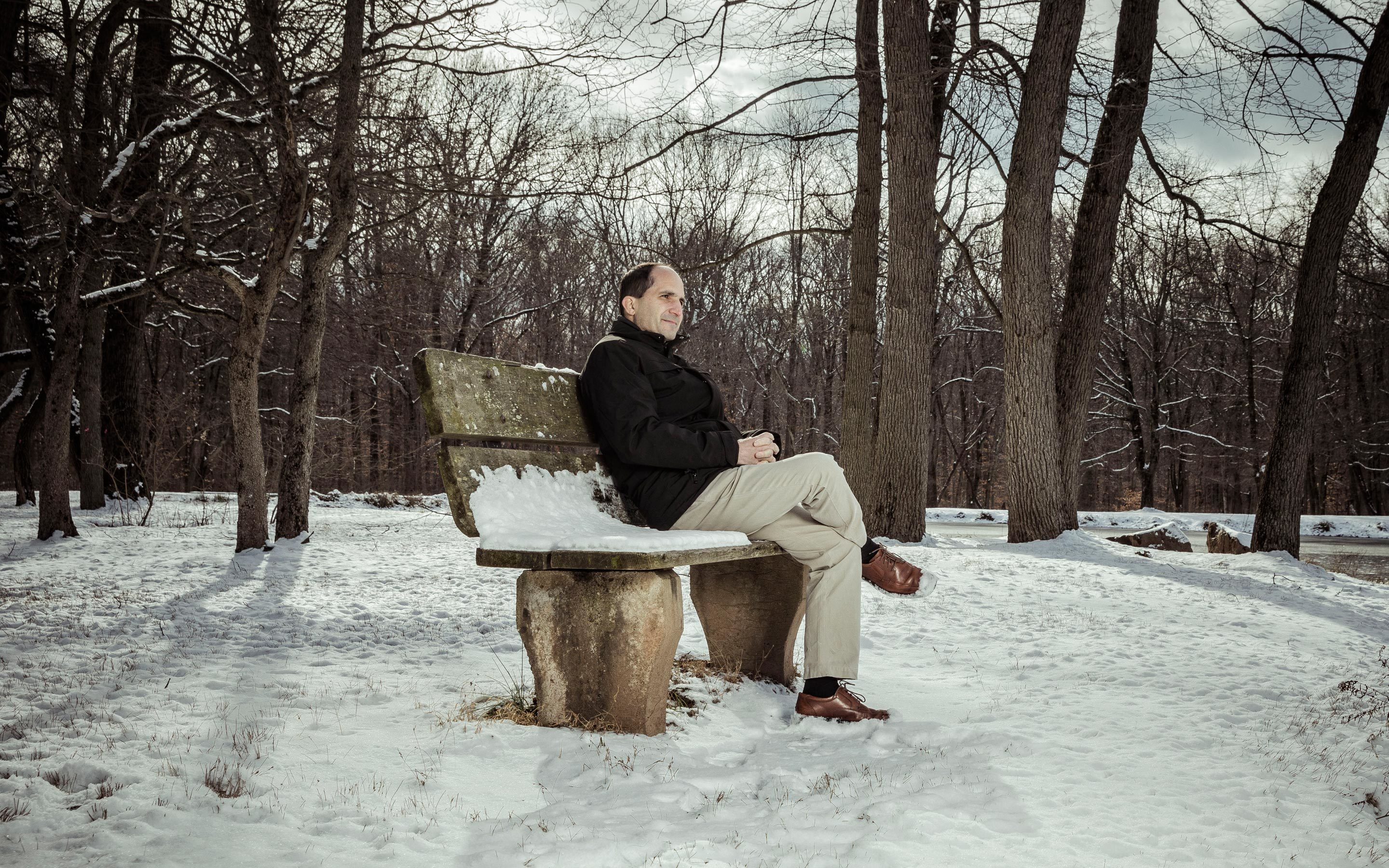 Juan Maldacena sitting by Institute Pond at the Institute for Advanced Study in Princeton, New Jersey, in January.