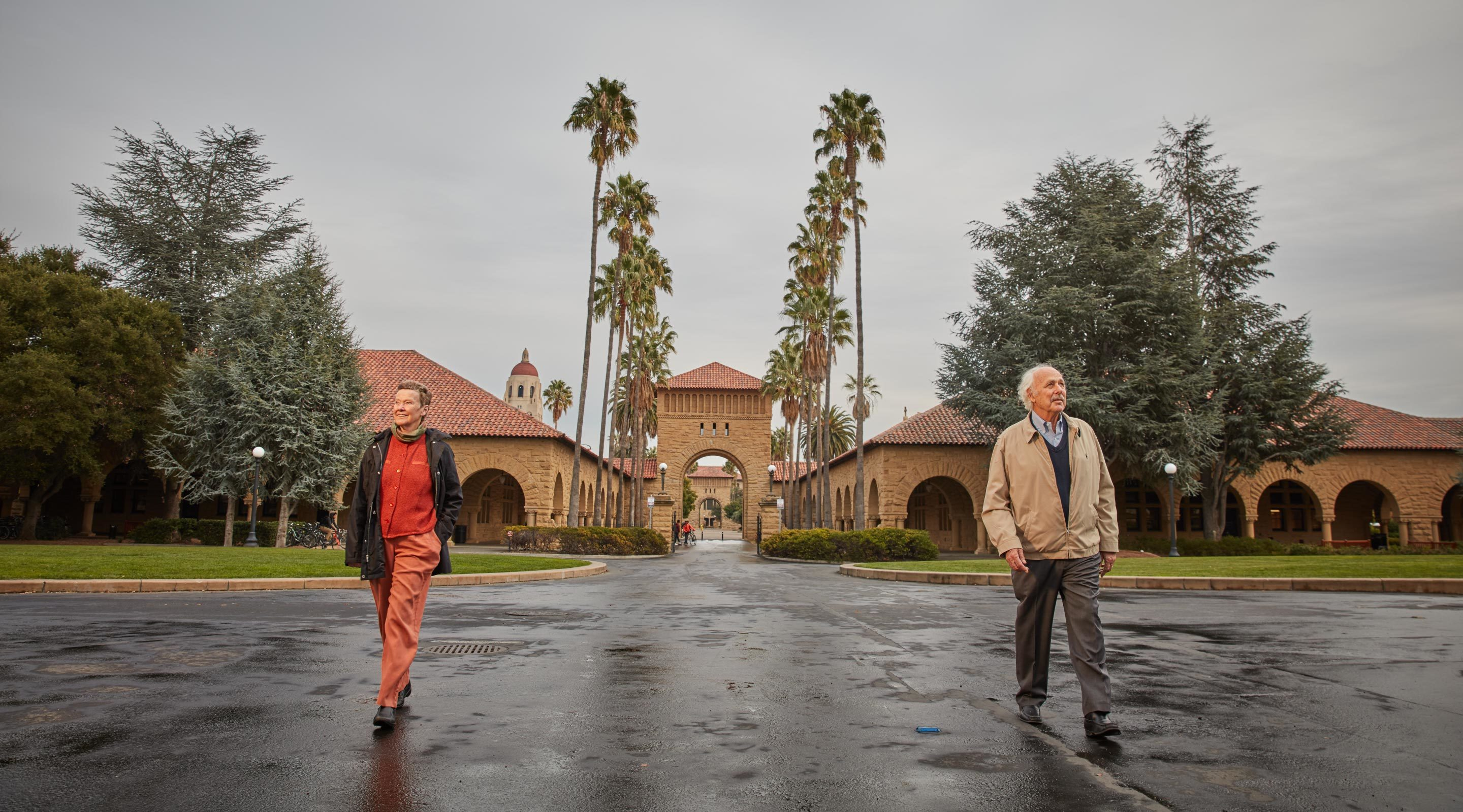 "Helen Quinn and Roberto Peccei walking toward Stanford University's new science and engineering quad. Behind them is the main quad, the oldest part of the campus. ""If you look at a campus map,"" said Quinn, who along with Peccei proposed Peccei-Quinn symmetry, ""you will see the axis that goes through the middle of both quadrangle areas. We are on that line between the two."""