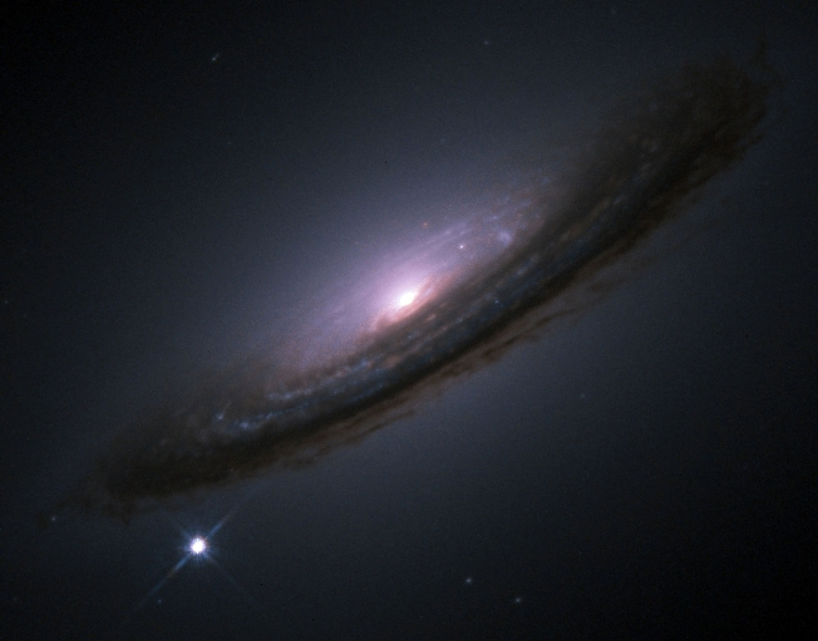 The Type Ia supernova 1994D glows in the lower left of this Hubble Space Telescope image of the spiral galaxy NGC 4526.
