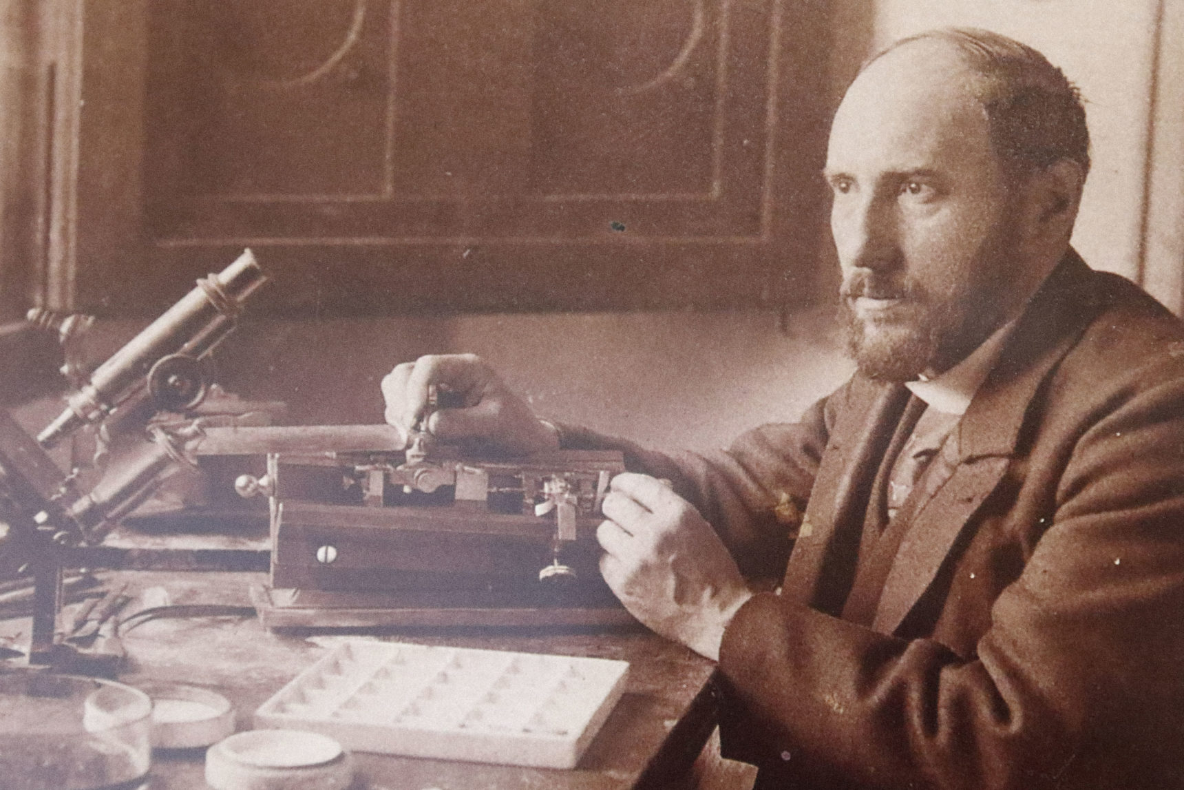 This early photograph of Santiago Ramón y Cajal at his desk (center) is likely a self-portrait. Cajal was an avid photographer who often experimented with black-and-white, color and stereographic images. The flanking images shows some of the tools he used in his work with microscopy. The collection of chemicals with which he stained tissues for microscopy is at left. The Golgi method that Cajal used to stain individual neurons is based on the same silver-nitrate chemistry that he used in developing his photographs. At right are Cajal's microtome, used for slicing brain tissue to make microscope slides, and his microscope.