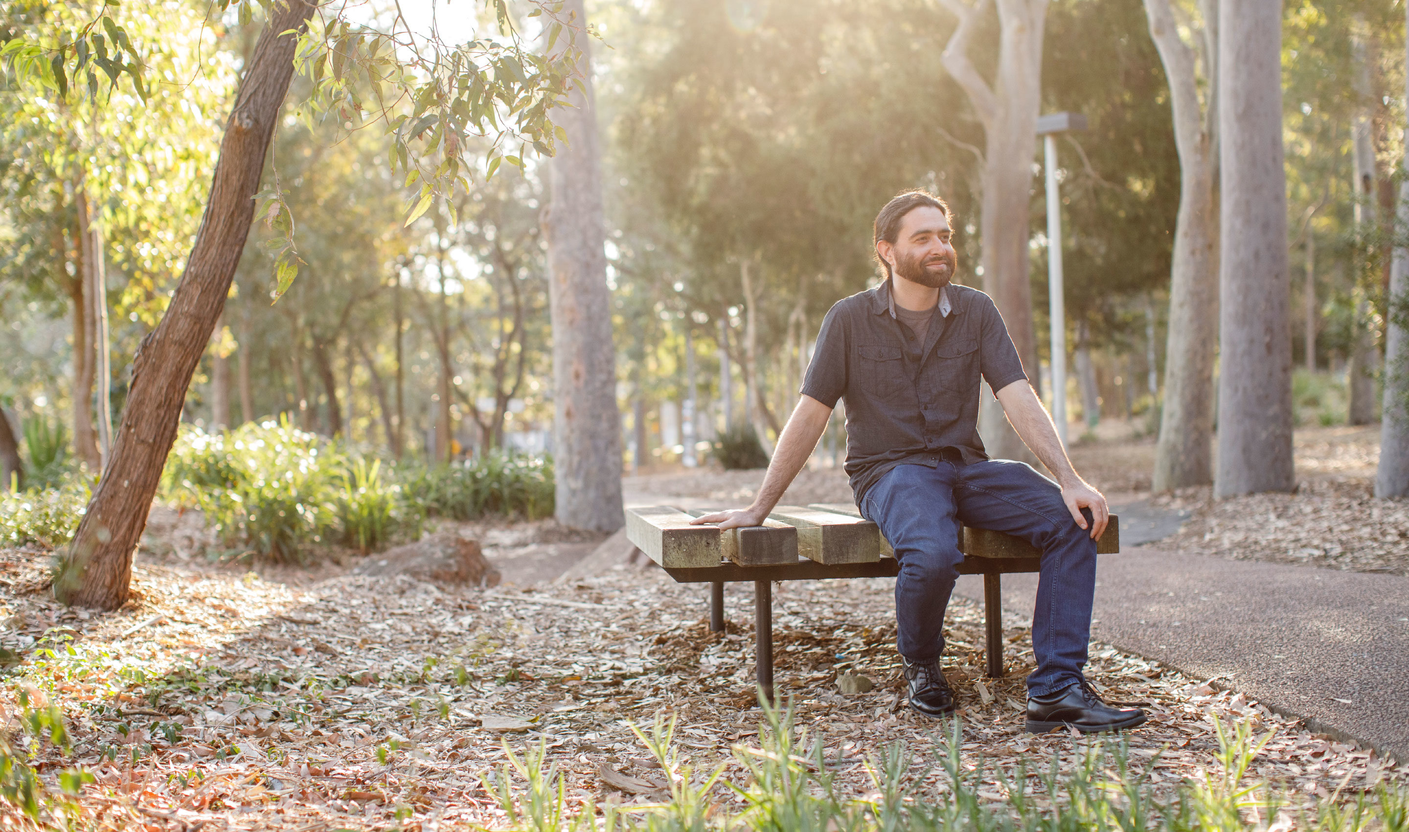 Micheal Assis in jeans and a blue shirt sitting outside on a bench