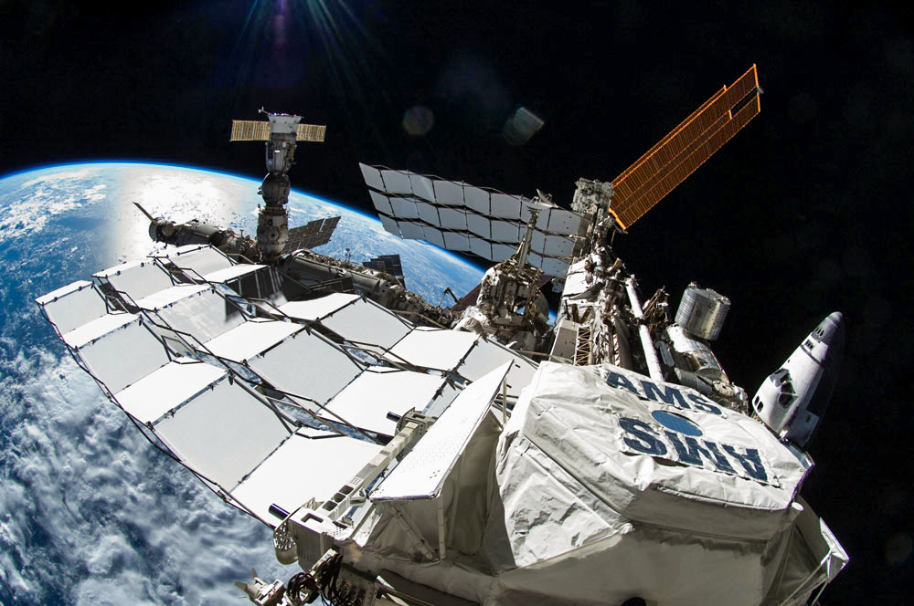 The Alpha Magnetic Spectrometer, seen here in the foreground of the International Space Station, could eventually settle the dark matter-vs.-pulsars debate.