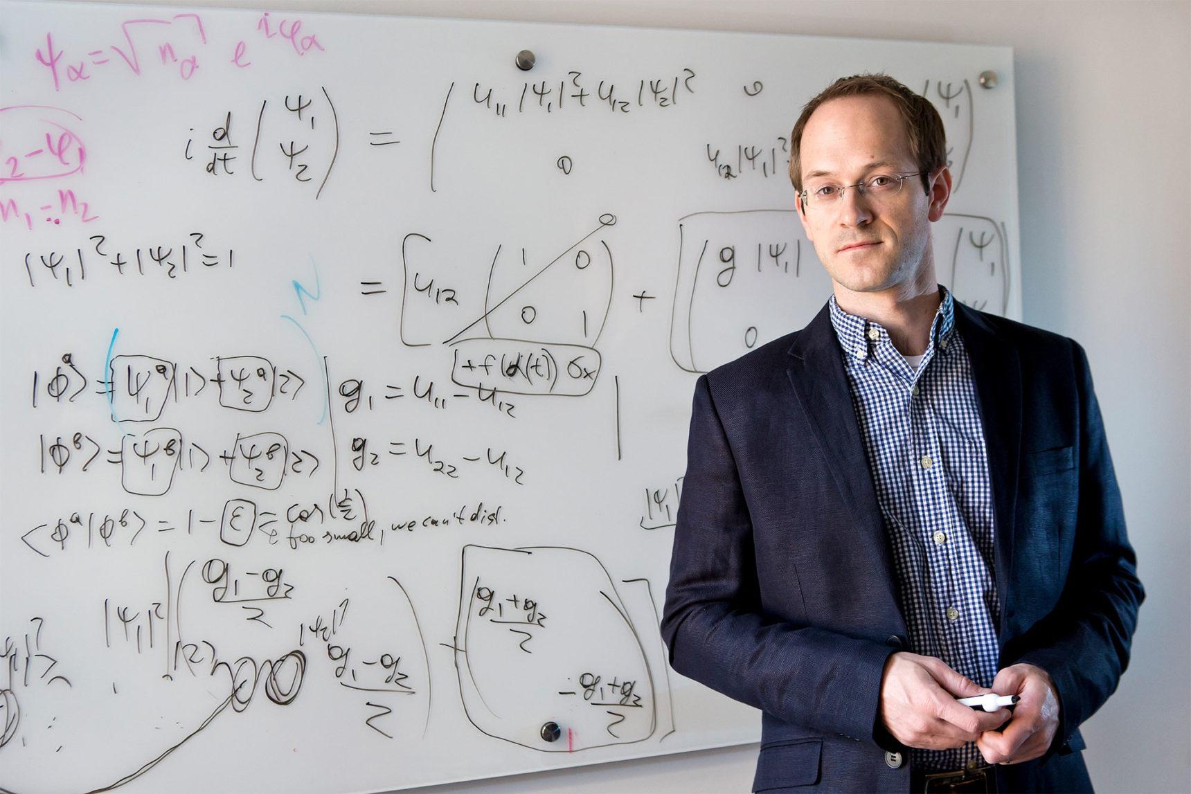 Foto de Andrew Childs de pie frente a una pizarra llena de matemáticas