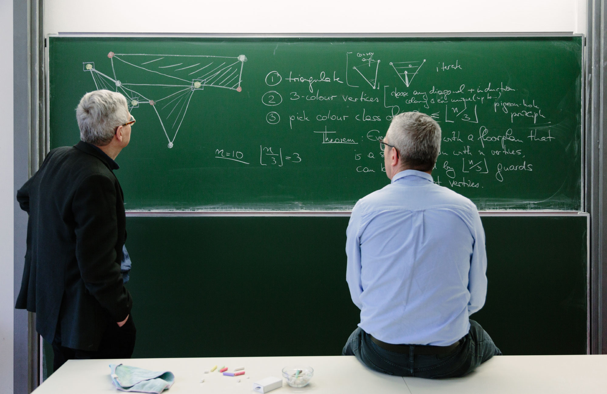 Mathematicians Prof. Günter M. Ziegler and Prof. Martin Aigner standing in front of a chalkboard