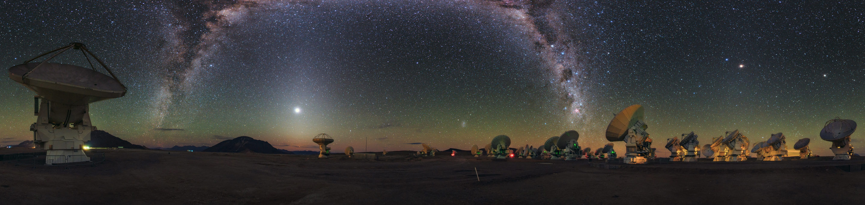 The ALMA Observatory's antennas appear to take in the sight of the Milky Way, arching like a galactic rainbow of dust and stars over the Chajnantor Plateau in the Chilean Andes