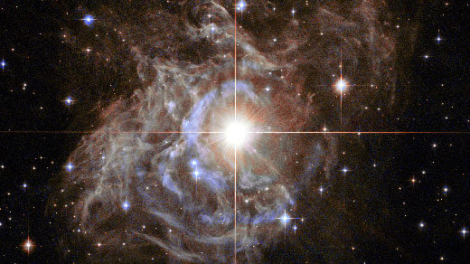 "Lede art for ""A Radically Conservative Solution for Cosmology's Biggest Mystery"": This Hubble image shows RS Puppis, a type of variable star known as a Cepheid variable. As variable stars go, Cepheids have comparatively long periods— RS Puppis, for example, varies in brightness by almost a factor of five every 40 or so days. RS Puppis is unusual; this variable star is shrouded by thick, dark clouds of dust enabling a phenomenon known as a light echo to be shown with stunning clarity. These Hubble observations show the ethereal object embedded in its dusty environment, set against a dark sky filled with background galaxies."