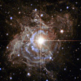 """Lede art for """"A Radically Conservative Solution for Cosmology's Biggest Mystery"""": This Hubble image shows RS Puppis, a type of variable star known as a Cepheid variable. As variable stars go, Cepheids have comparatively long periods— RS Puppis, for example, varies in brightness by almost a factor of five every 40 or so days. RS Puppis is unusual; this variable star is shrouded by thick, dark clouds of dust enabling a phenomenon known as a light echo to be shown with stunning clarity. These Hubble observations show the ethereal object embedded in its dusty environment, set against a dark sky filled with background galaxies."""