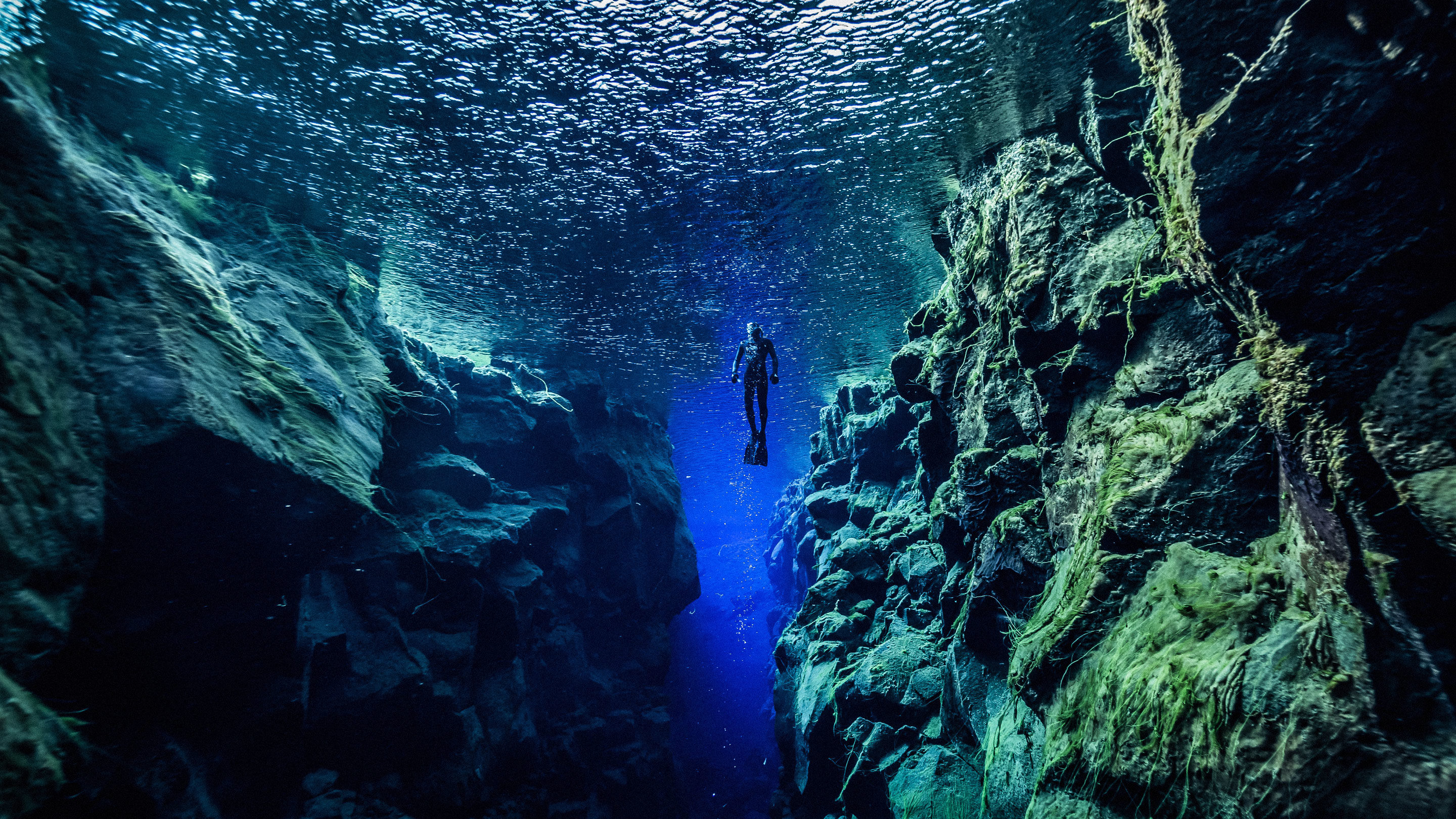 Photo of a diver between two tectonic plates in Silfra. reykjavik. Iceland