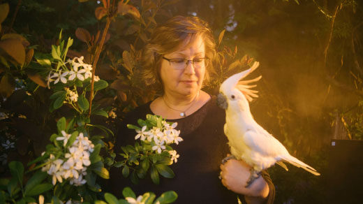 Victoria Meadows in her garden with her cockatoo.