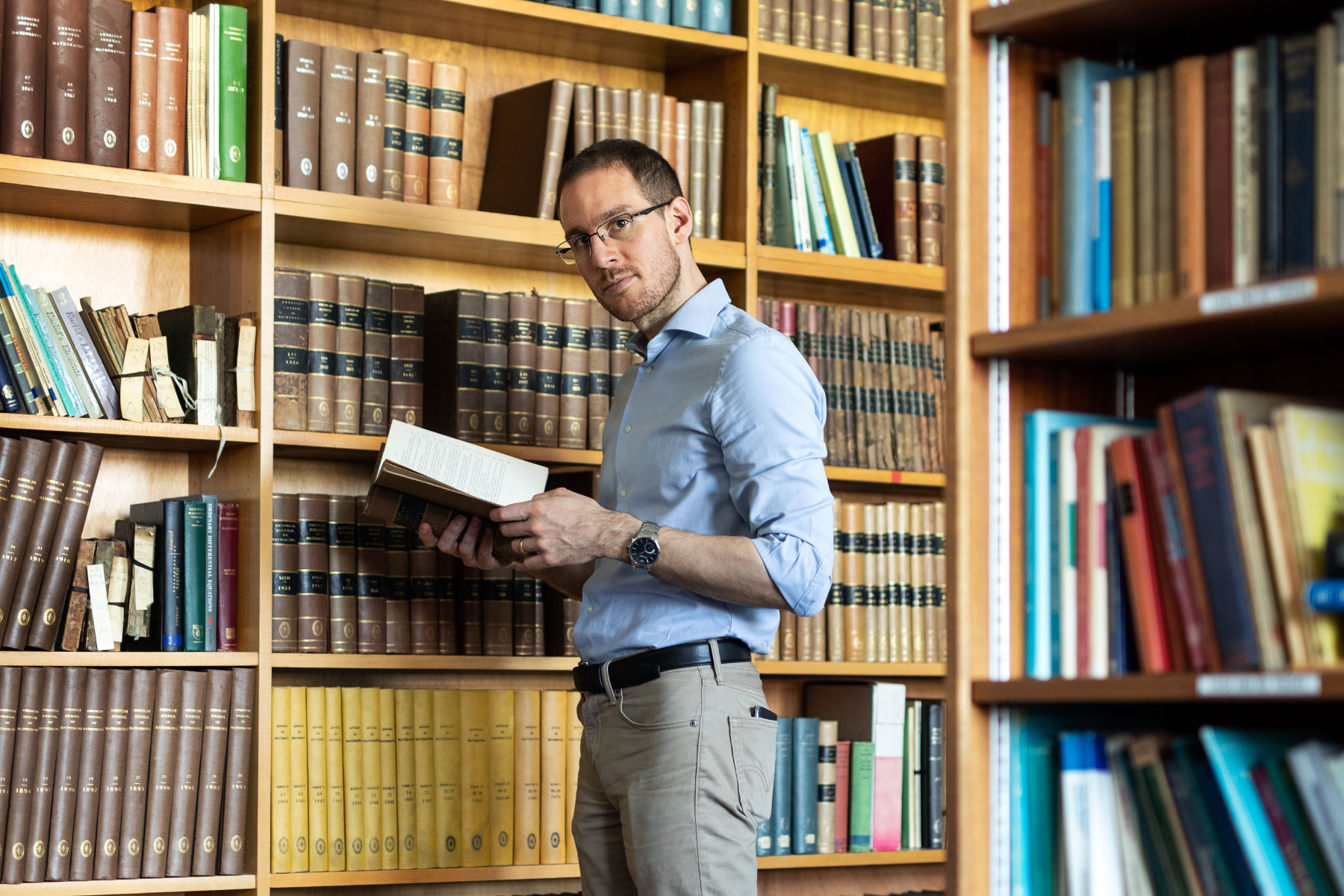 Photo of Alessio Figalli looking at Journals in the Library of Maths Department at Durham University