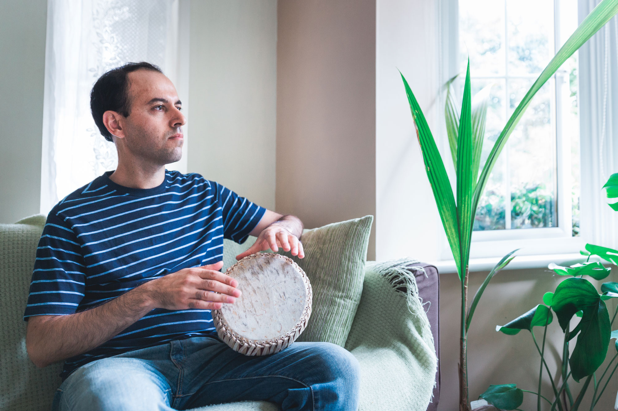 Caucher Birkar plays self-taught Kurdish beats on a small Thai drum in his family home near Cambridge, England