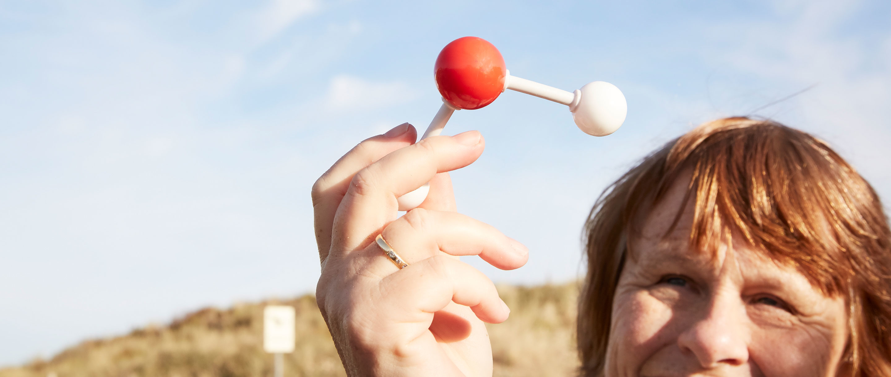 Ewine van Dishoeck at Noordwijk beach in the Netherlands, holding up a water molecule model.