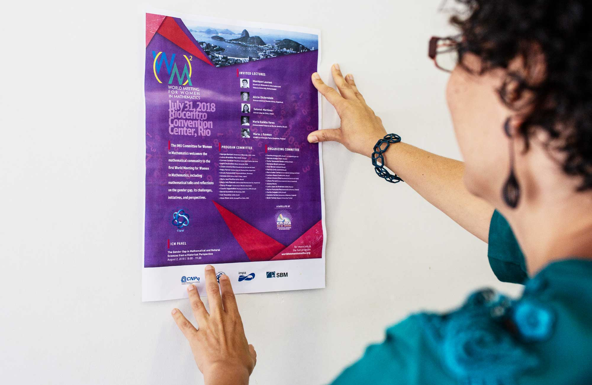 Carolina Araujo holding a poster for the World Meeting for Women in Mathematics