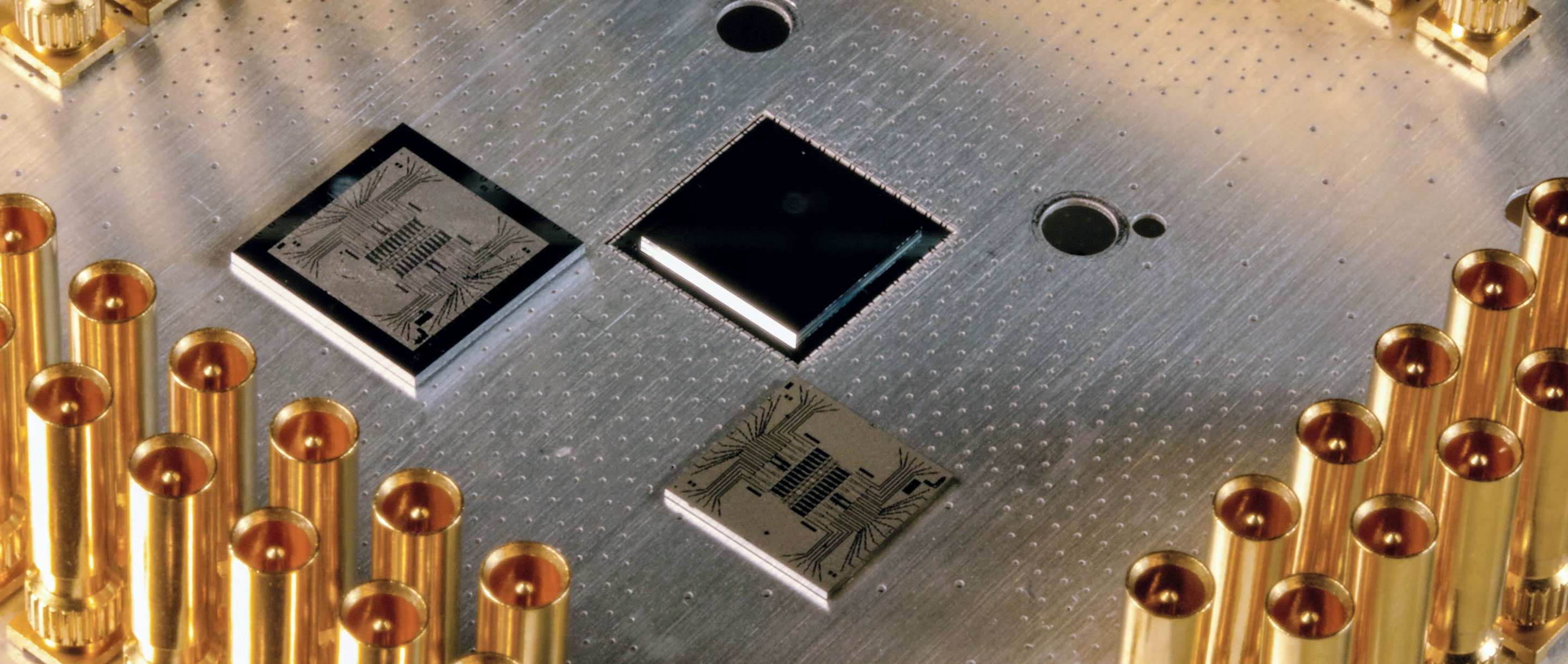 Photo of a silver metal plate with chips mounted on its surface.