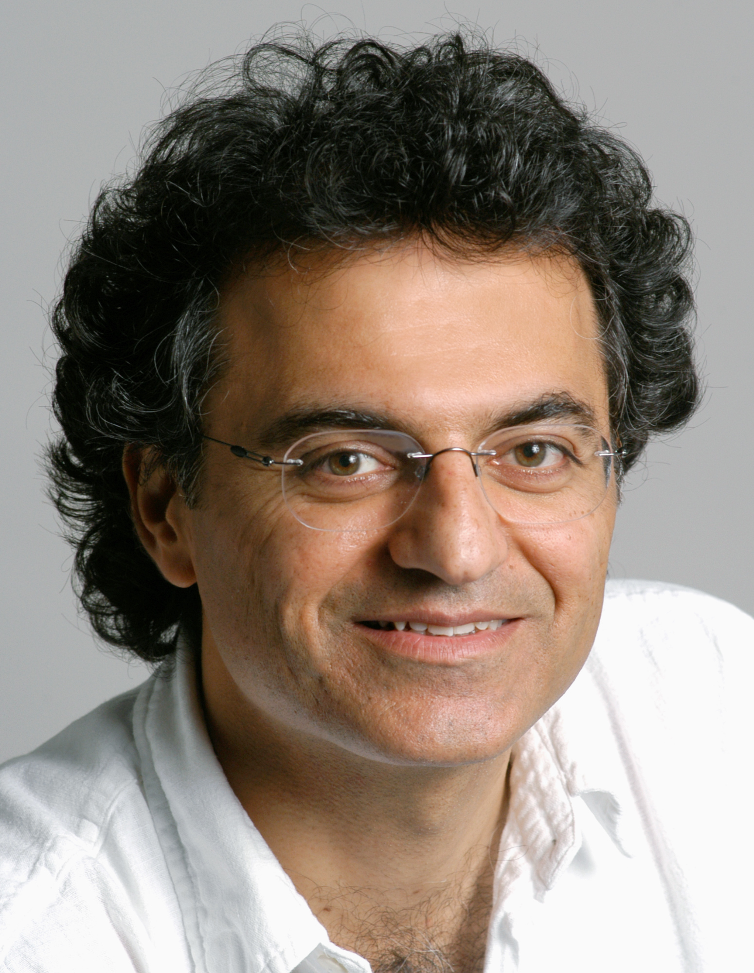 Photo of a man wearing thin wireframe glasses, a white shirt, short black curly hair, smiling and looking into the camera.