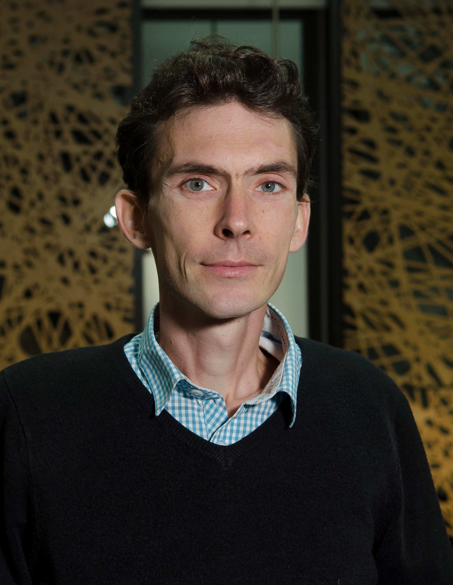 Photo of a man wearing a lightblue checkered collar shirt with a black jumper over it, looking into the camera.