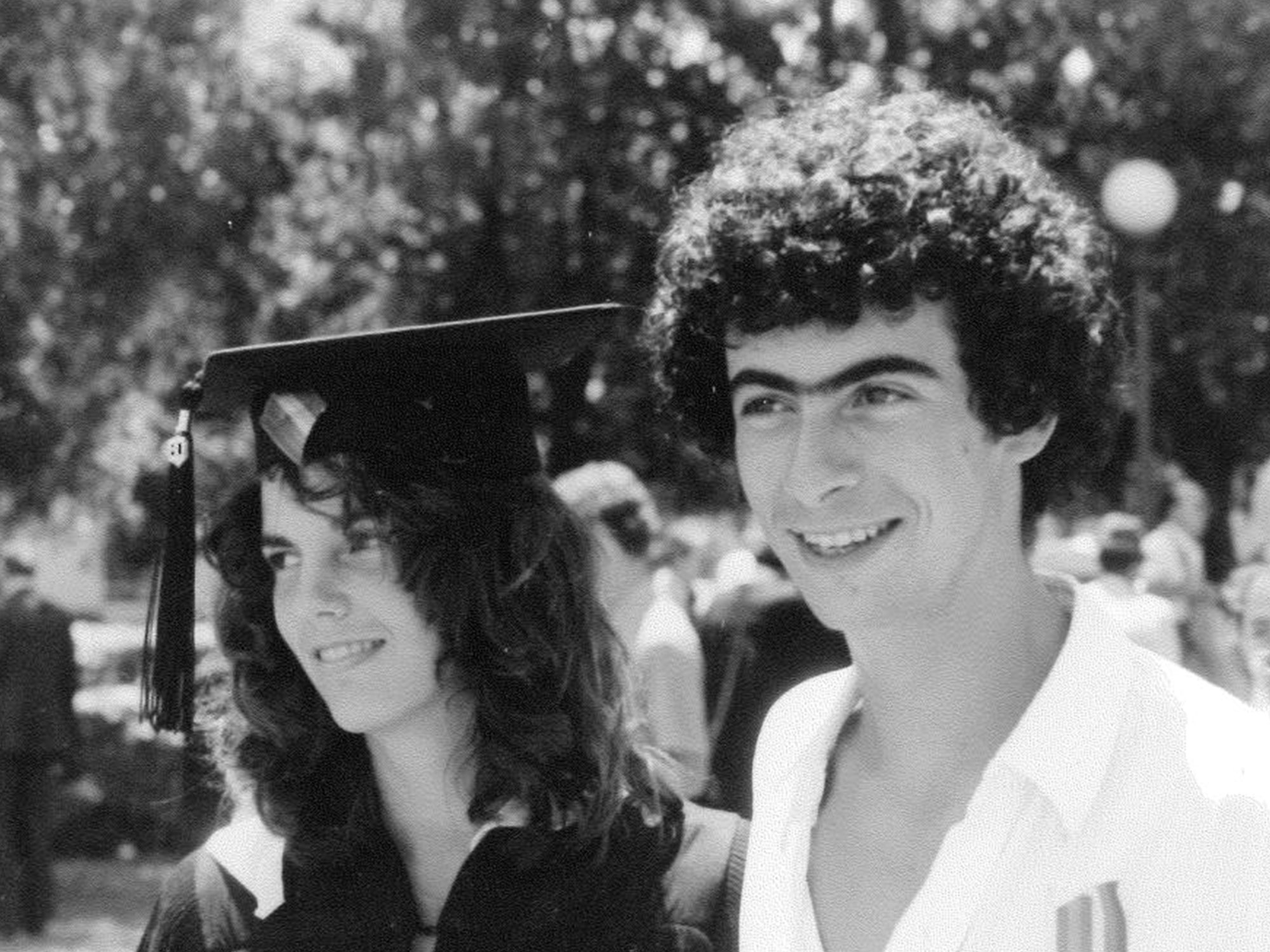 Black-and-white photo of Ann Nelson and David Kaplan standing side by side and smiling, with people and trees in the background. She is wearing a cap and gown; he is not.