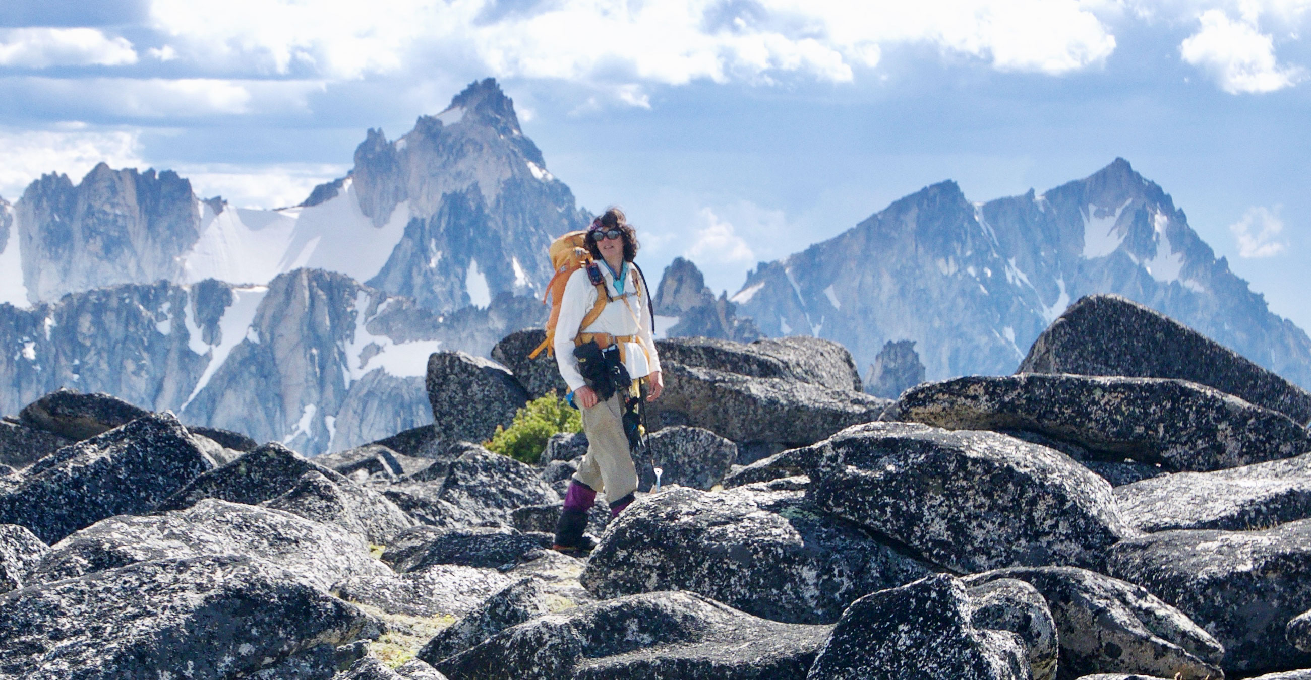 Ann Nelson in hiking gear traversing some boulders at the top of a mountain with snowy peaks in the background.