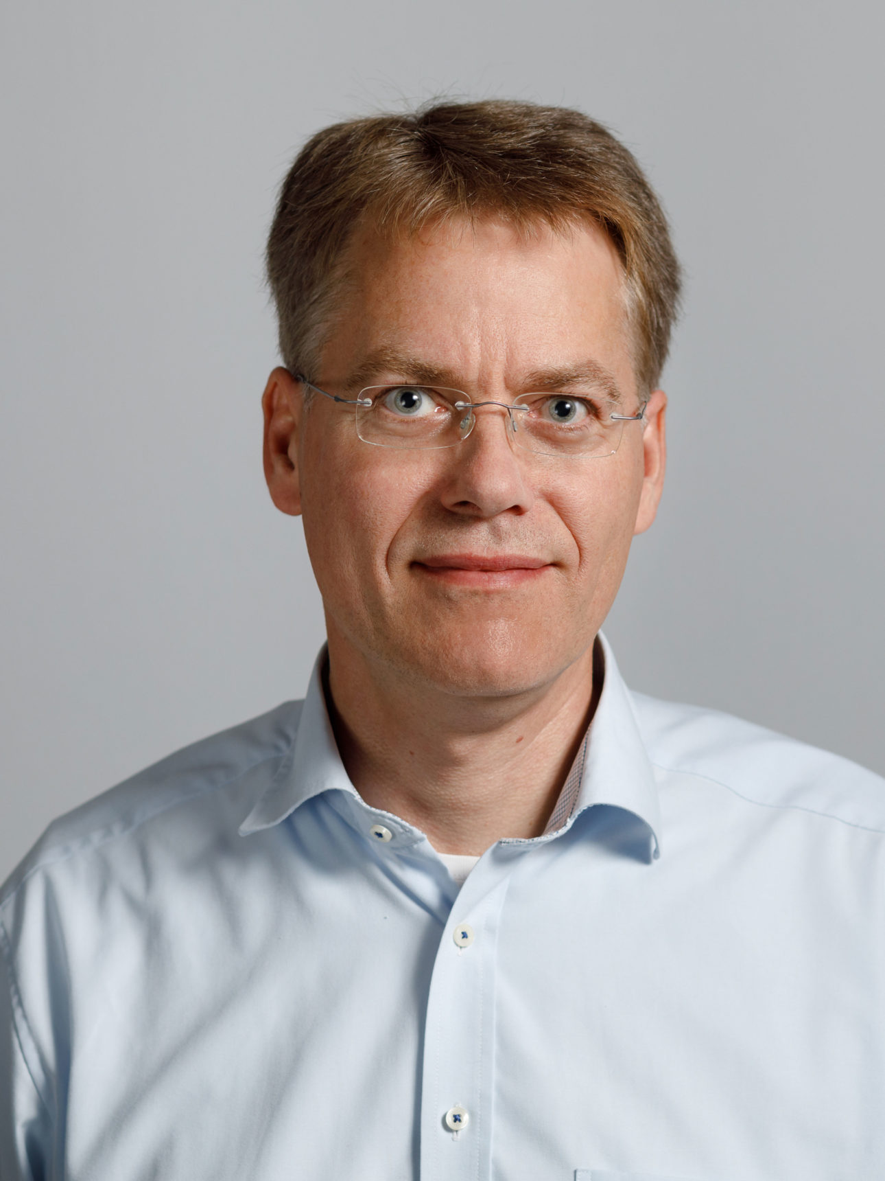 Portrait of a man with light colored eyes, wearing a pale blue button-down shirt, rimless glasses, smiling while looking straight into the camera.