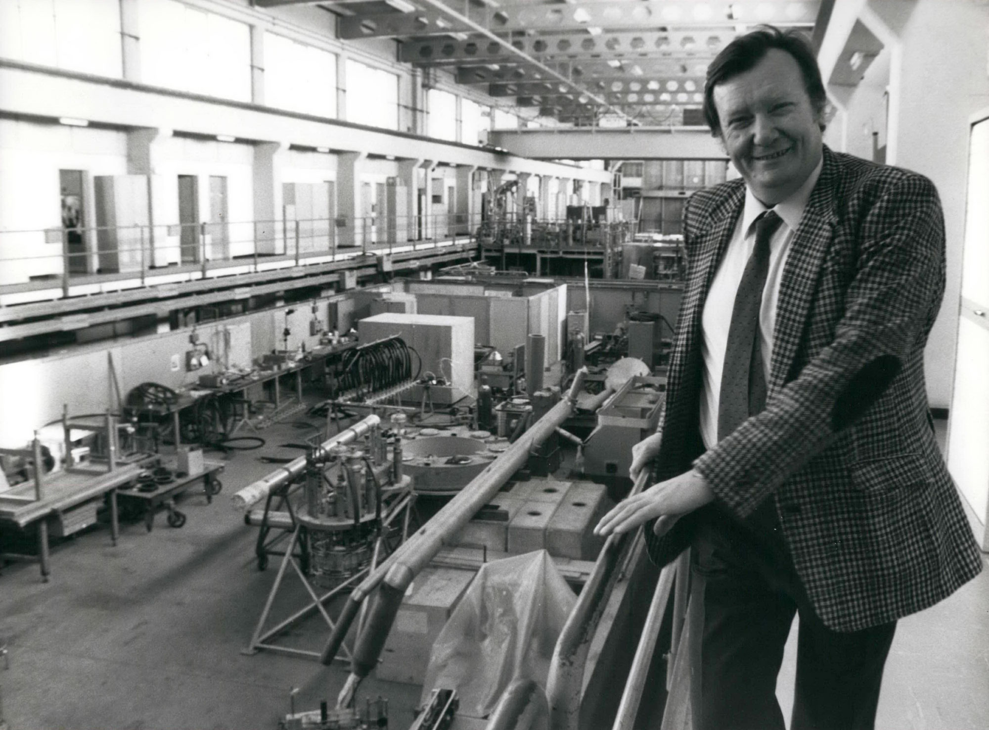 Black and white photo of a young Carlo Rubbia smiling in a suit and tie, standing on a walkway at CERN laboratory in 1984 with equipment behind him.