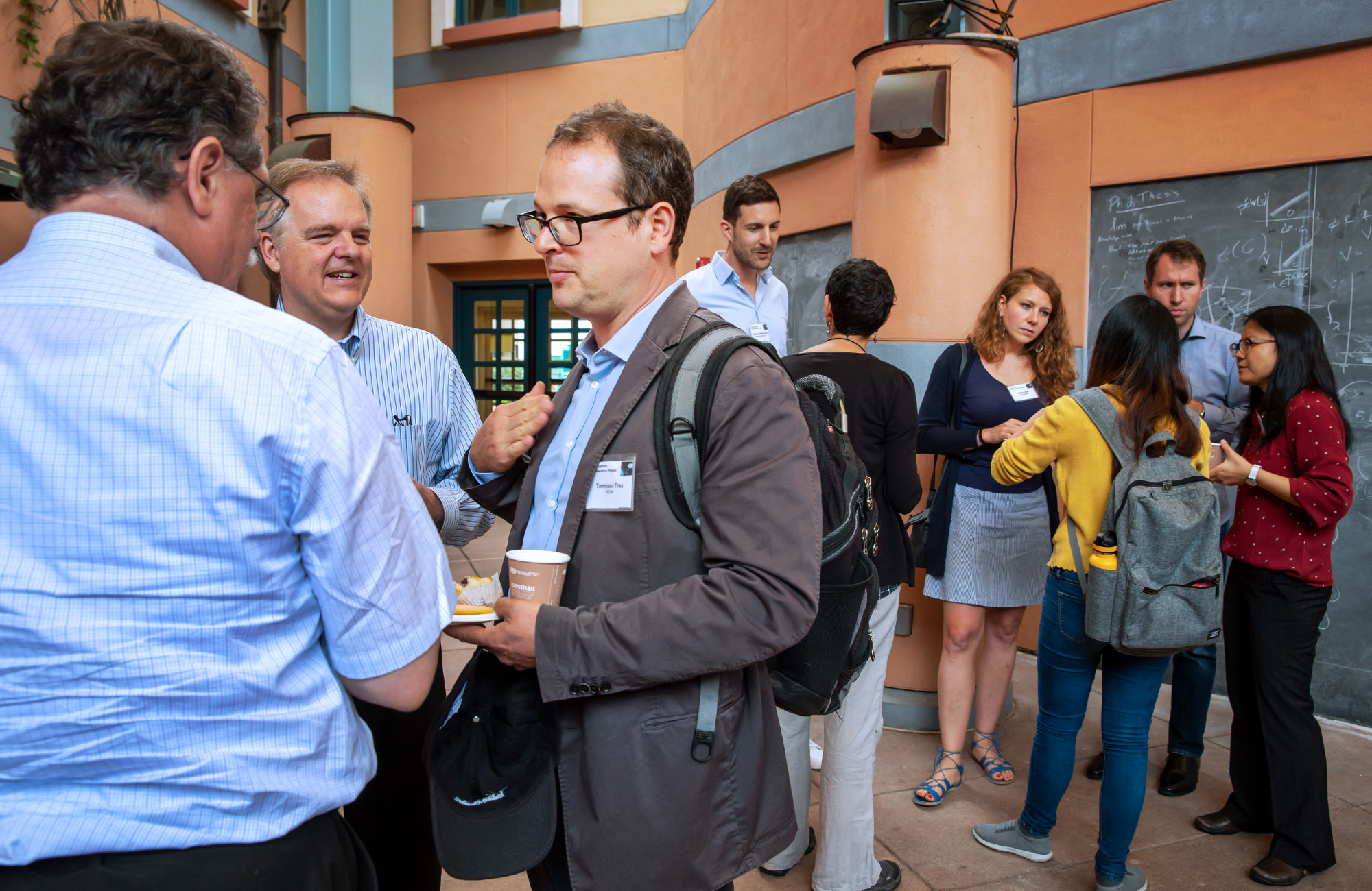 Tomasso Treu holding a cup of coffee and chatting with fellow cosmologists in a courtyard at the Kavli Institute for Theoretical Physics.