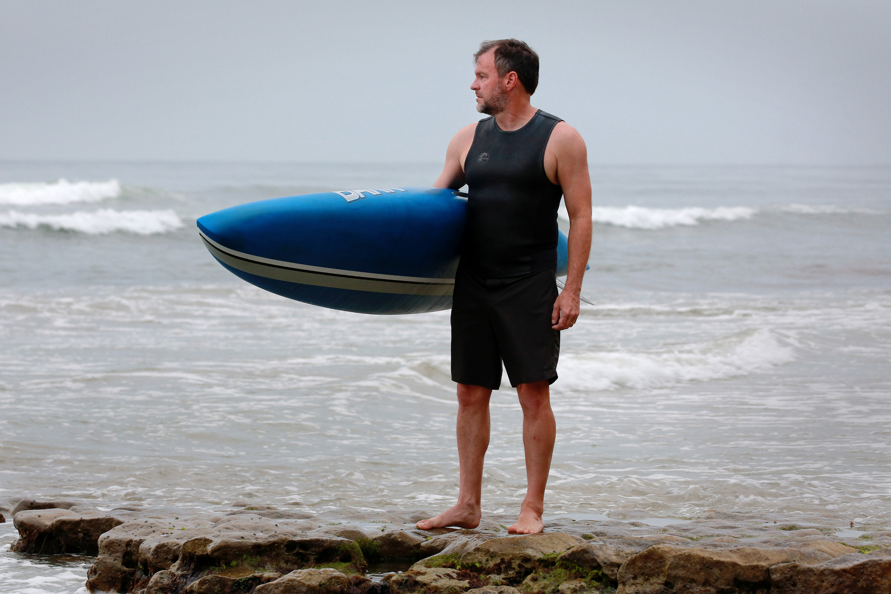 Craig Callender holding a paddleboard at the beach.