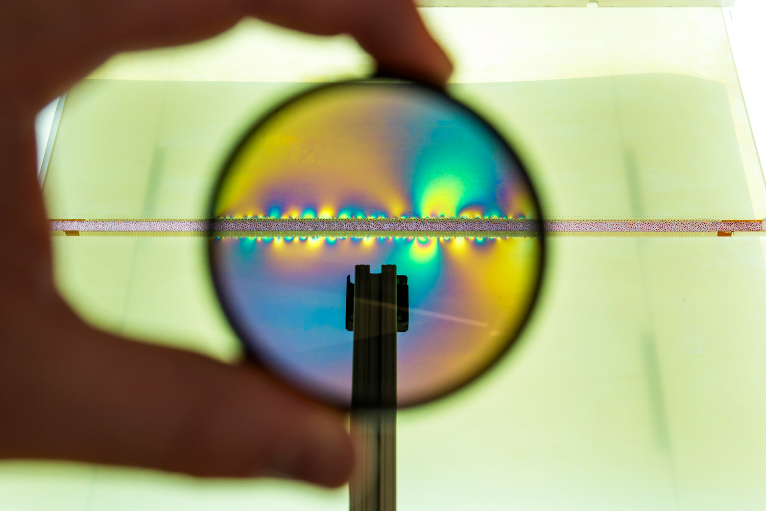 A hand holds a lens in front of the seam between two plastic blocks. Through the lens, colorful light emanates from stress points in the seam.