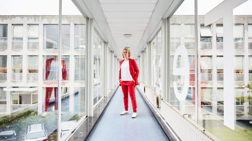 Stephanie Wehner in a red suit standing in a glass-paneled corridor at Delft University of Technology in the Netherlands. Her reflection appears in the glass to the right and left.