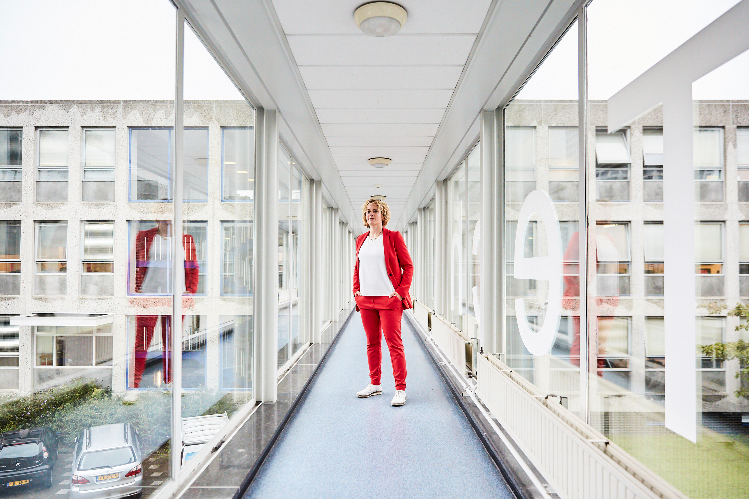 Stephanie Wehner in a red suit standing in a glass-paneled corridor at Delft University of Technology in the Netherlands. Her reflection appears in the glass to the right and left.]