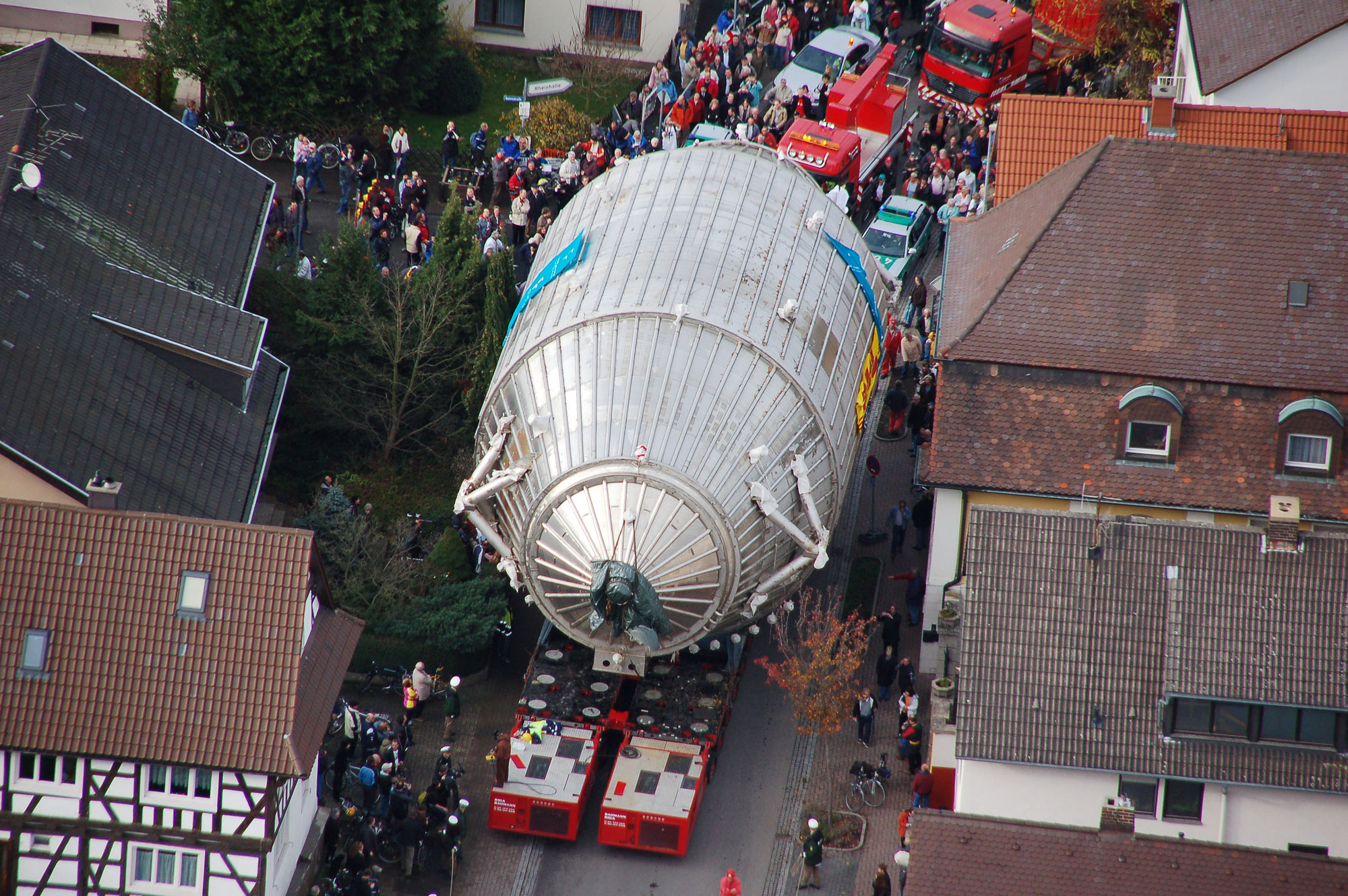 A large, egg-shaped metallic structure is seen from above as red emergency vehicles transport it through a quaint European village.
