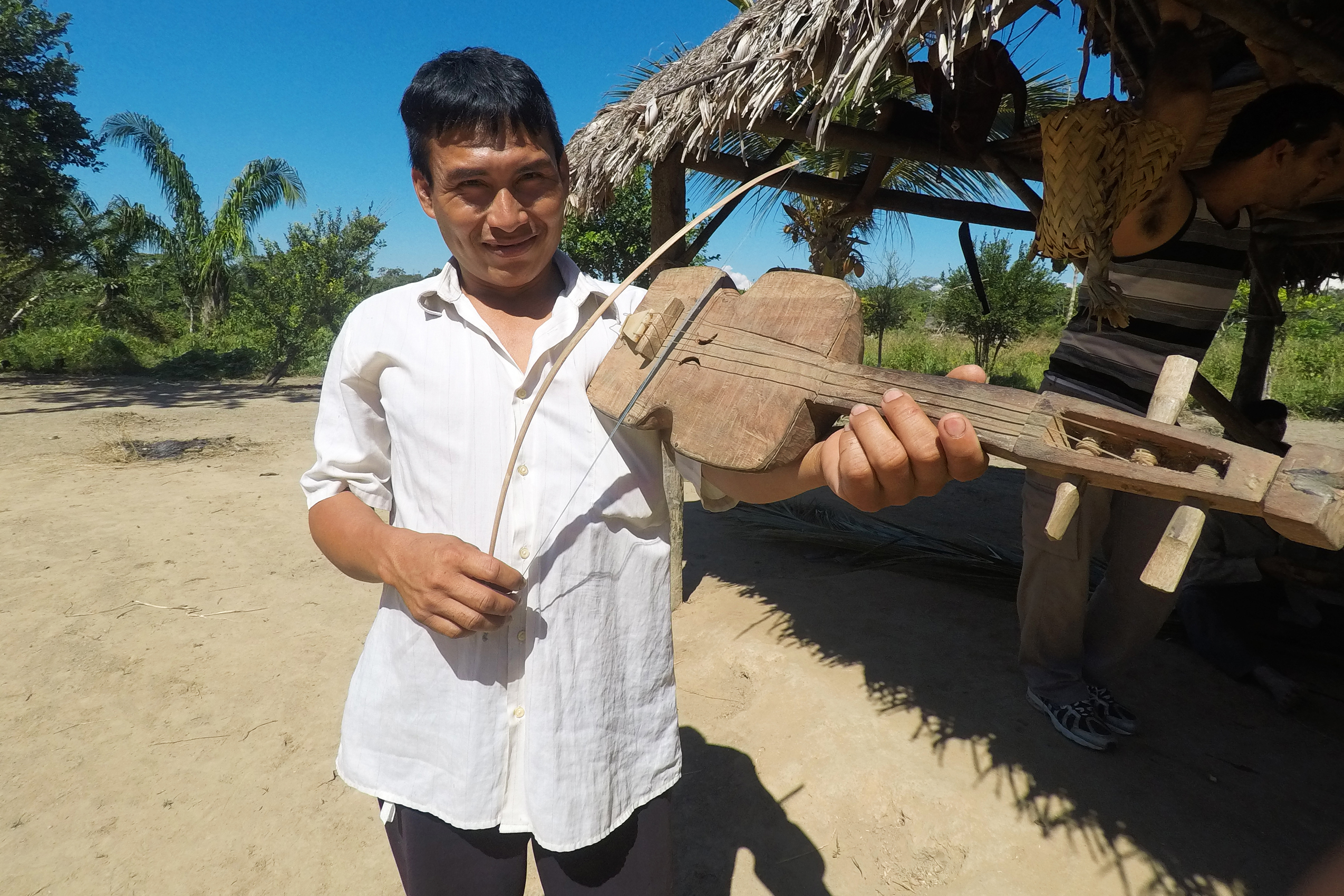 A Tsimané man plays an instrument resembling a violin.