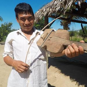 A Tsimané man plays an instrument resembling a violin.