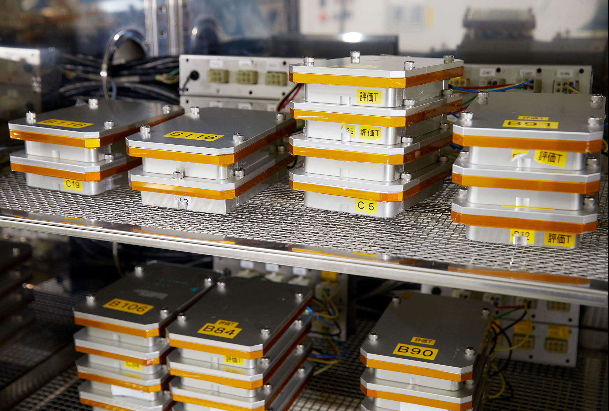 Stacks of unmounted lithium-ion batteries on metal shelves.