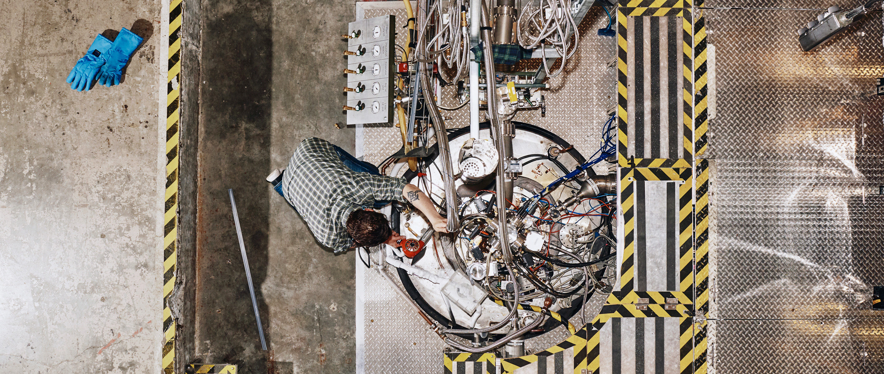 An overhead shot of an engineer working on a metal tank with pipes and cables coming out of it.