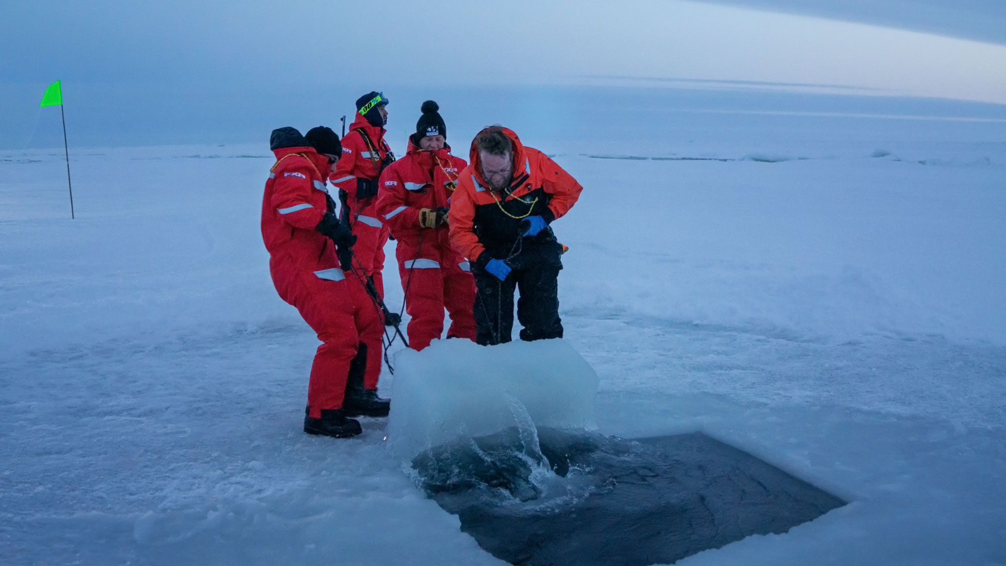 Scientists open a hole in arctic ice.