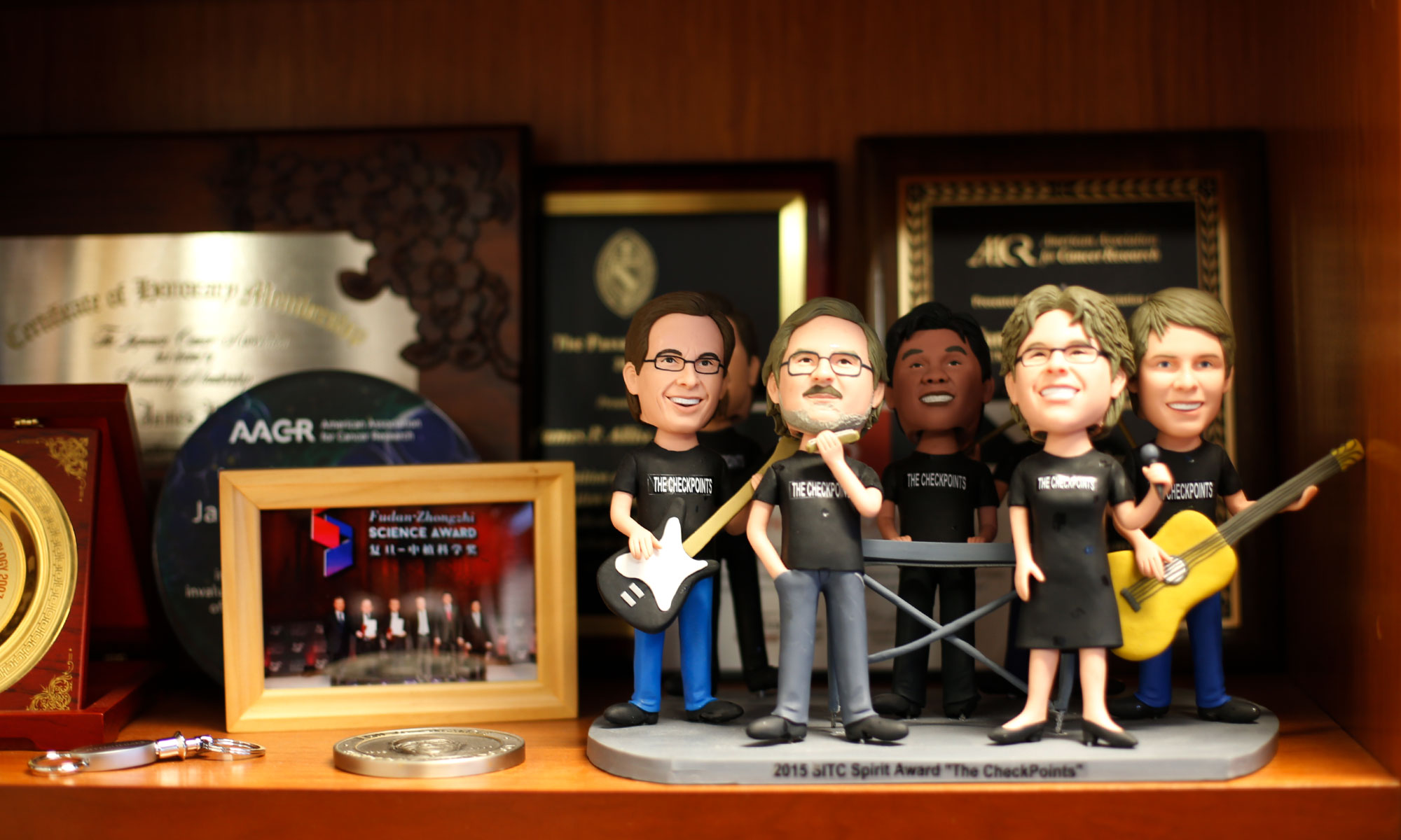 A bobblehead of Jim Allison and his band on a shelf with many awards.