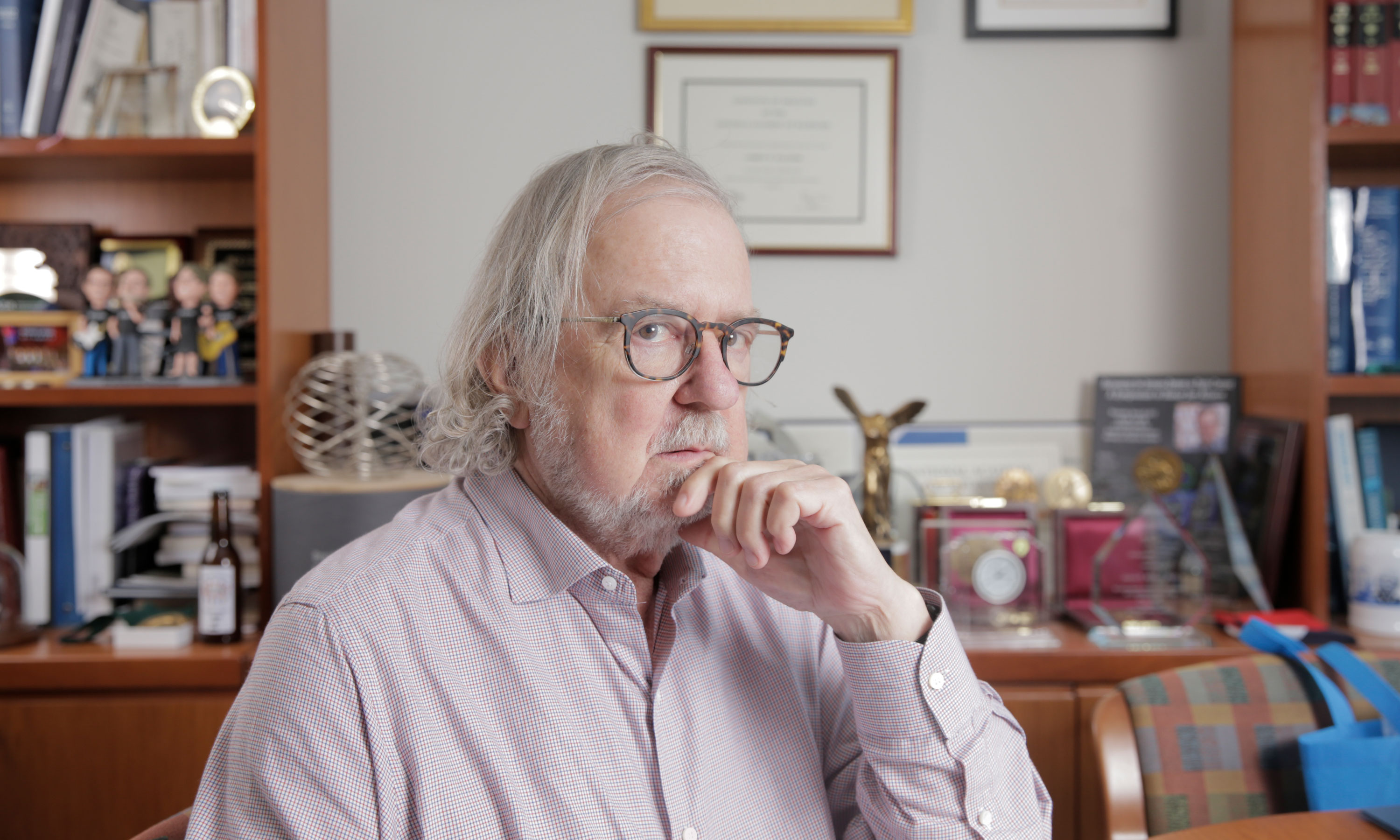 Photo of James P. Allison sitting at his desk at the MD Anderson Cancer Center.