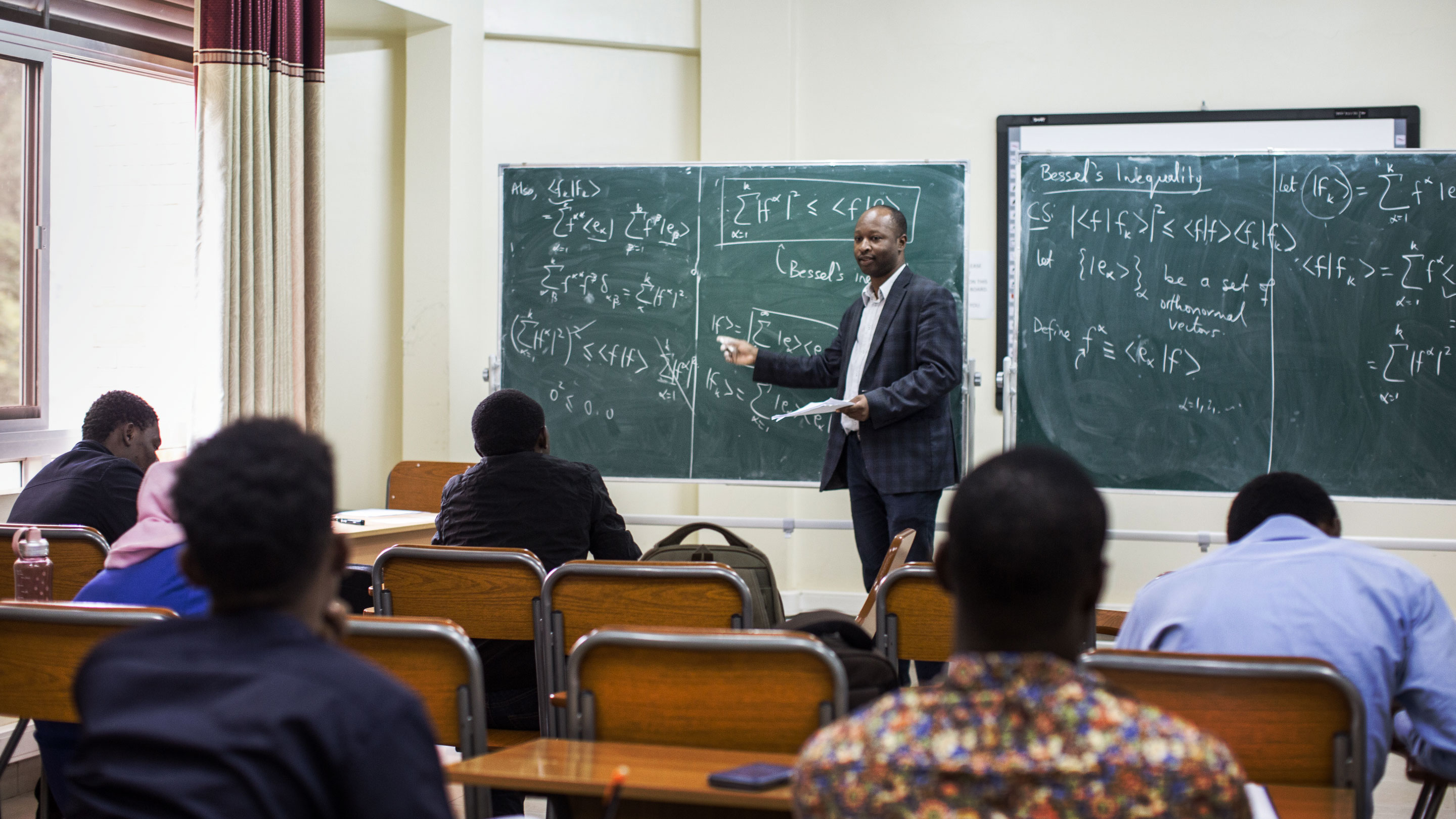 Omololu Akin-Ojo in a blue checked suit standing at the front of a class, gesturing toward equations on a green chalkboard.