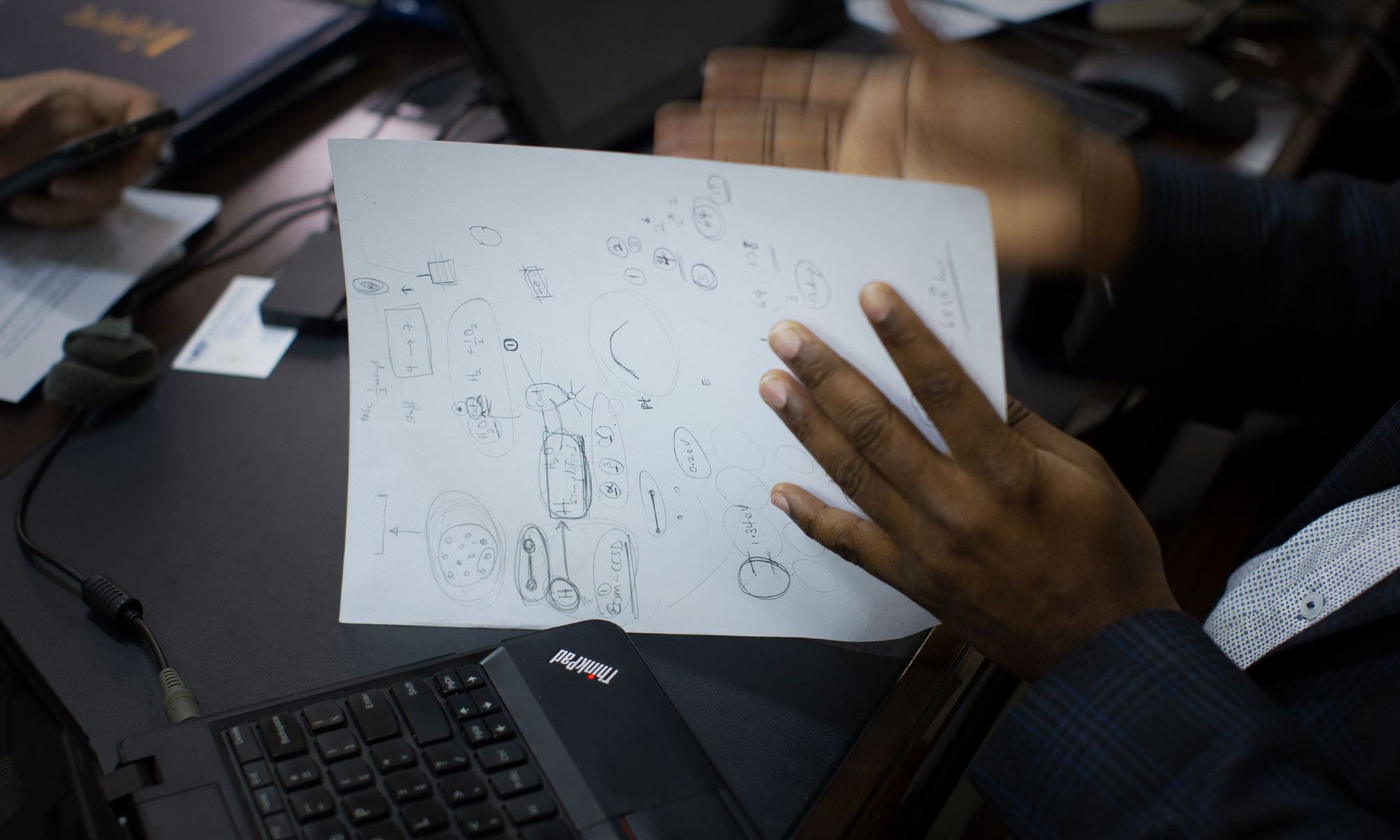 Close-up of a page of drawings and calculations, next to a gesturing hand.