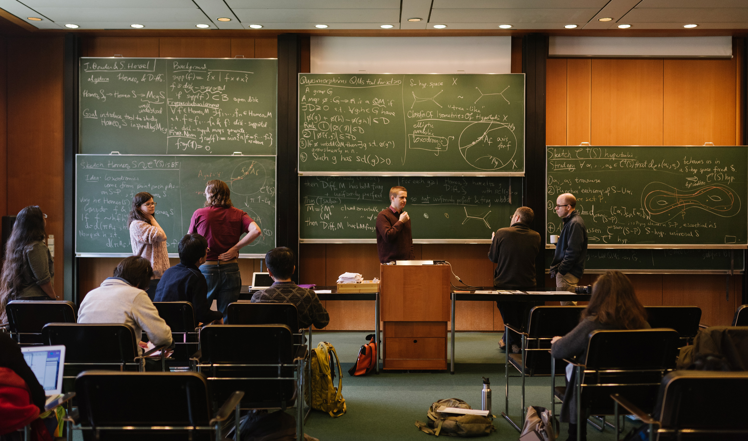 Photo of mathematicians standing and sitting in front of various chalkboards full of mathematics