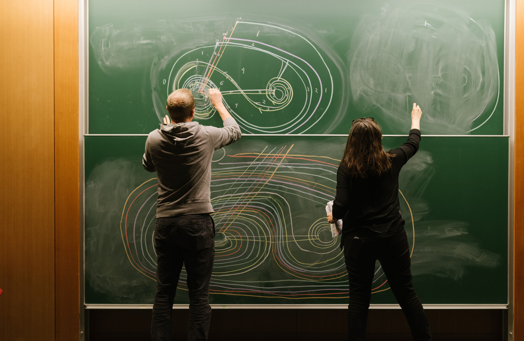 Photo of two mathematicians drawing on a chalkboard