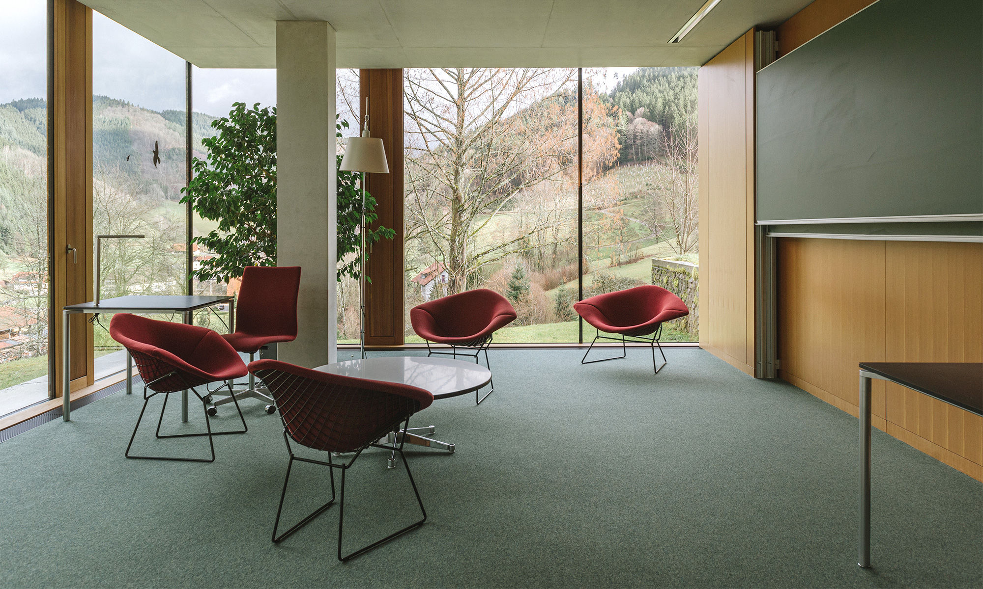 Photo of chairs, tables and a chalkboard at Oberwolfach, in front of a wide window revealing forests outside
