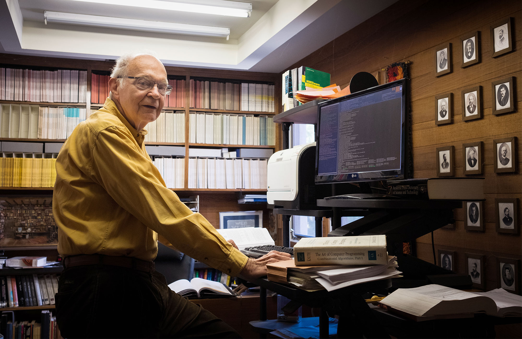Photo of Donald Knuth at a computer in his home, in front of shelves of books and a wall full of portraits