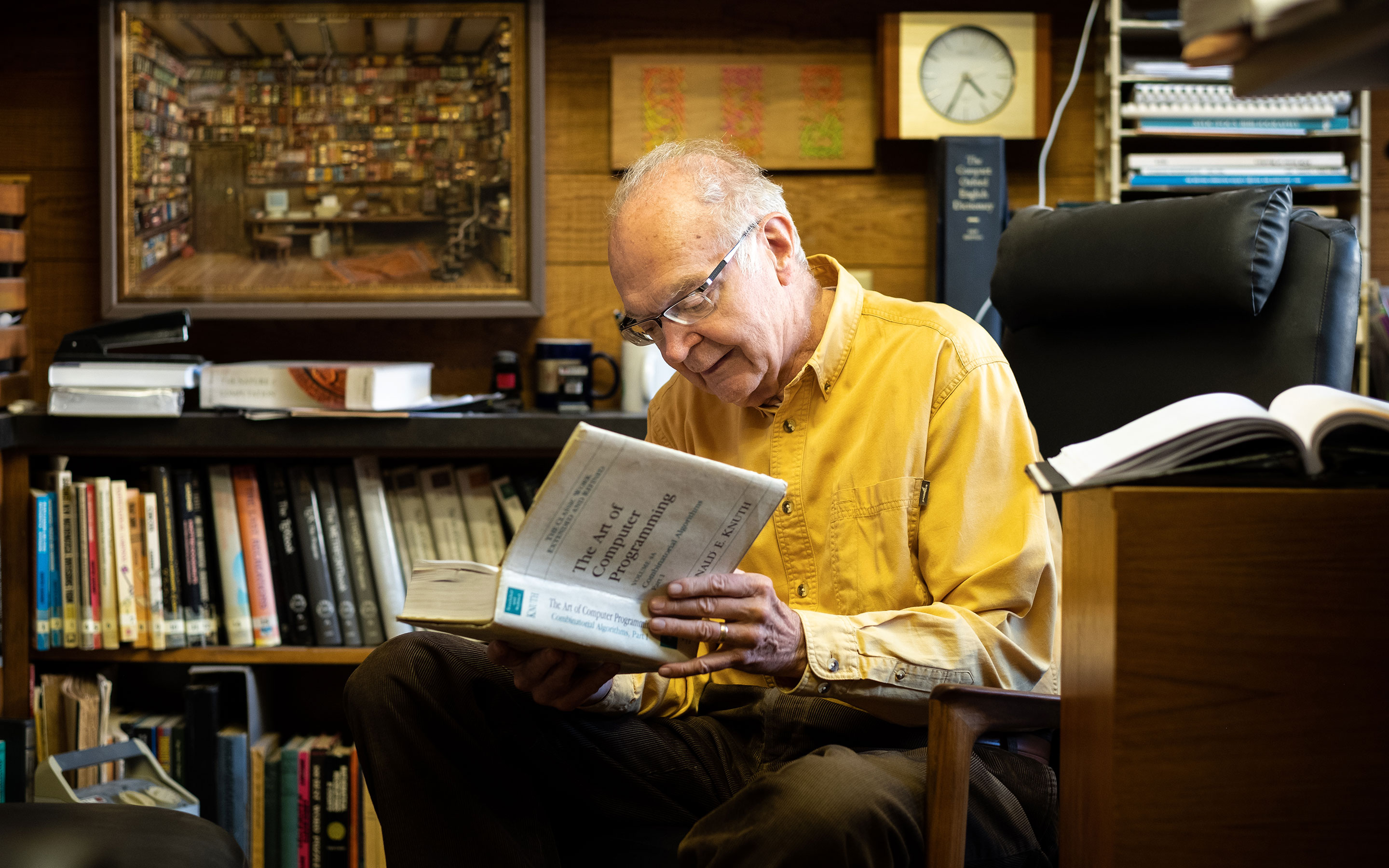 Photo of Donald Knuth in a yellow shirt sits and reads from a volume of The Art of Computer Programming