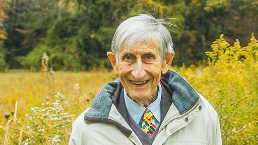 Photo of Freeman Dyson standing in a meadow in front of a forest