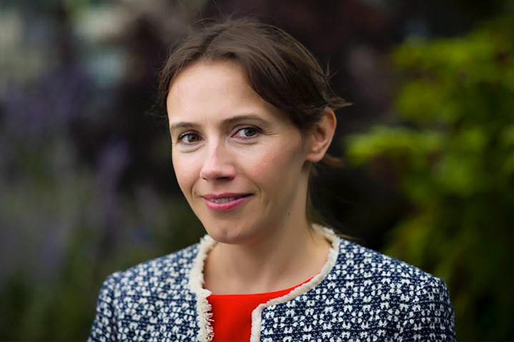 Portrait photo of Aiofe McLysaght, a geneticist at Trinity College Dublin, standing outside.
