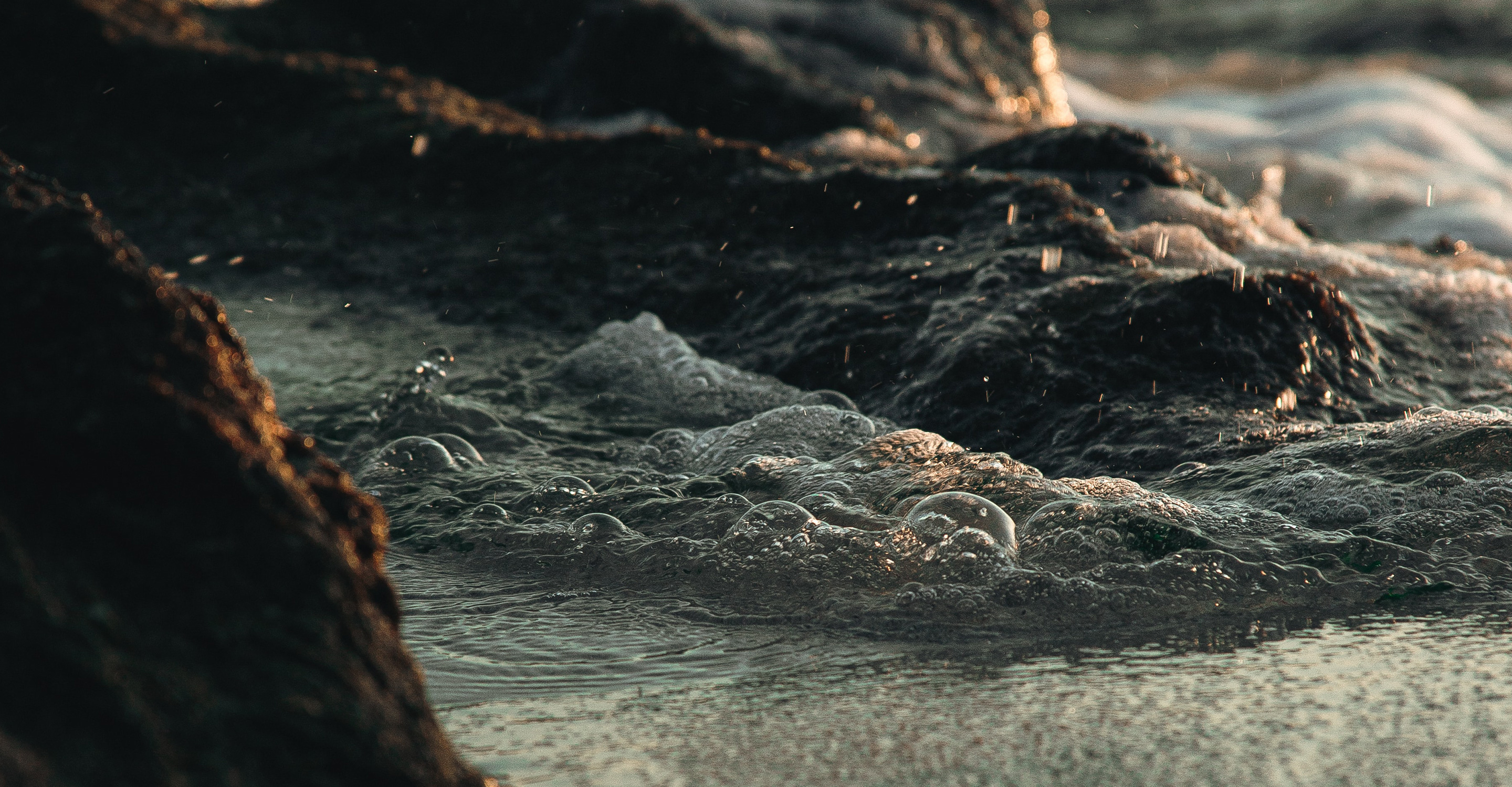 Close-up of water swirling among rocks at the sea's edge.