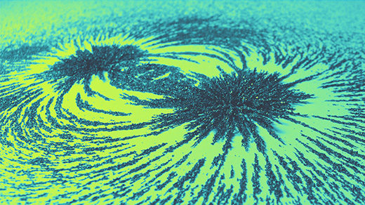 Photo of iron filings spread along magnetic field lines on a green and yellow background
