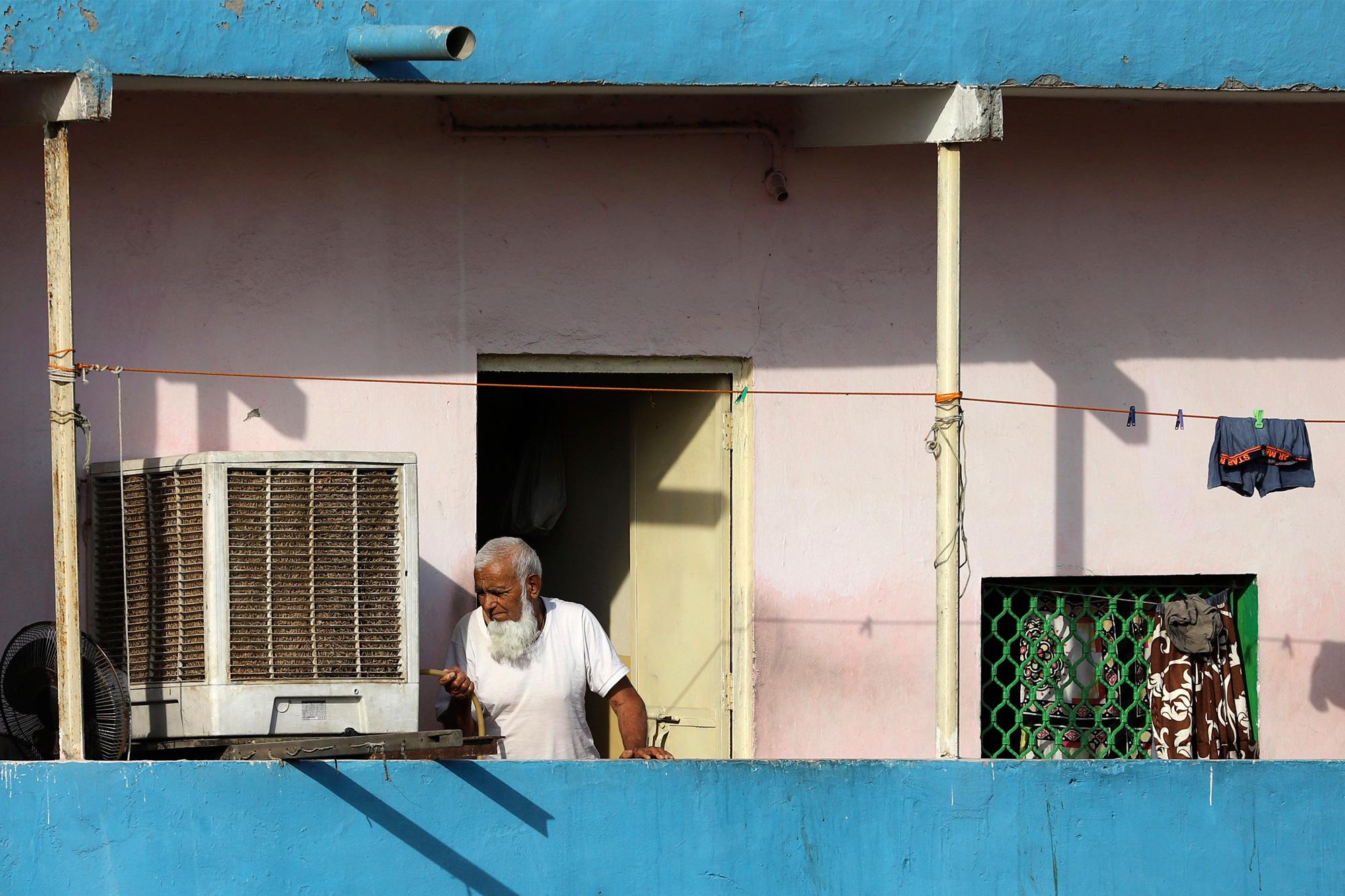 Older man on a balcony pours himself water in Delhi.